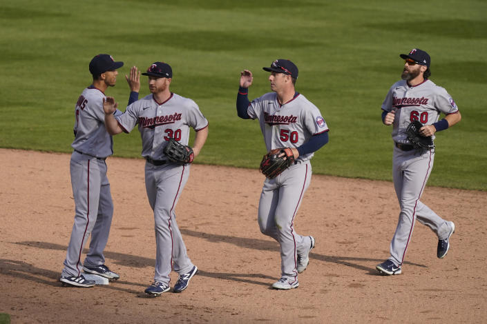 Minnesota Twins shortstop Andrelton Simmons, left, greets outfielders Kyle Garlick (30), Brent Rooker (50) and Jake Cave after their win over the Detroit Tigers in a baseball game, Monday, April 5, 2021, in Detroit. (AP Photo/Carlos Osorio)