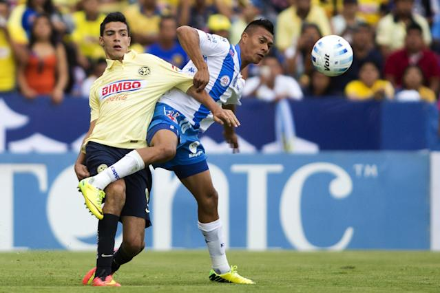 Raul Jimenez (L) of America vies for the ball with Michael Orozco (R) of Puebla during their Mexican Apertura tournament football match at the Cuauhtemoc stadium on August 2, 2014, in Puebla City (AFP Photo/Victor Straffon)