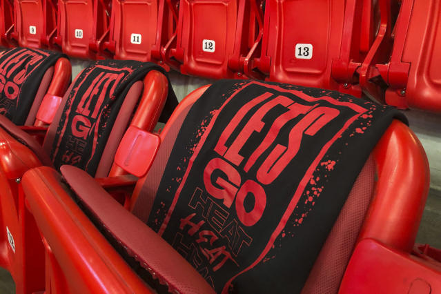 "FILE - In this Oct. 23, 2019, file photo, ""Let's Go Heat"" is displayed on t-shirts in the stands as the Miami Heat and the Memphis Grizzlies practice before an NBA basketball in Miami, Fla. There's a clear desire for basketball to resume but, perhaps mindful of how rushing back too quickly hurt other leagues around the world, the NBA seems to be taking very cautious baby steps back to the court. (AP Photo/Brynn Anderson, File)"