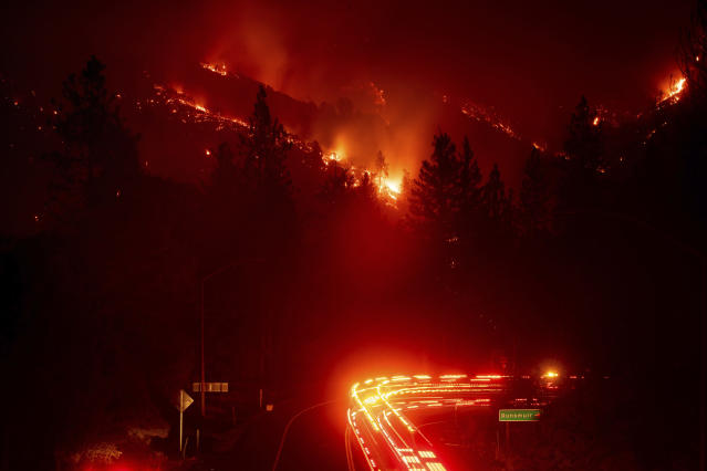 <p>Fire trucks pass the Delta Fire burning in the Shasta-Trinity National Forest, Calif., on Wednesday, September 5, 2018. Parked trucks lined more than two miles of Interstate 5 as both directions remained closed to traffic. (AP Photo/Noah Berger) </p>
