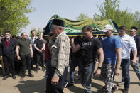 Men carry a coffin of Elvira Ignatieva, an English language teacher, in Kazan, Russia, Wednesday, May 12, 2021, who was killed at a school shooting on Tuesday. Russian officials say a gunman attacked a school in the city of Kazan and Russian officials say several people have been killed. Officials said the dead in Tuesday's shooting include students, a teacher and a school worker. Authorities also say over 20 others have been hospitalised with wounds. (AP Photo/Dmitri Lovetsky)