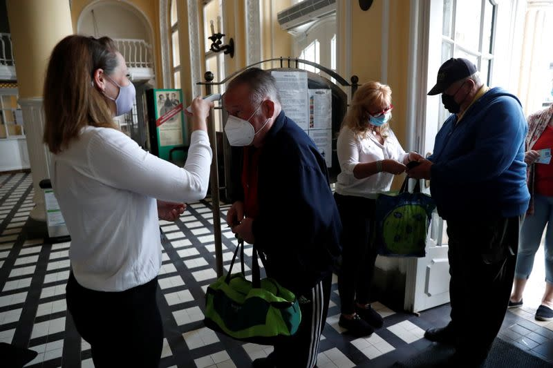An employee checks the temperature at the Szechenyi thermal bath as the coronavirus disease (COVID-19) restrictions are eased in Budapest