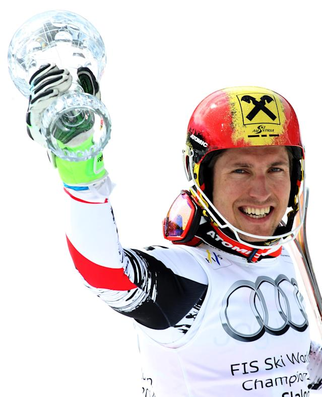 Austria's Marcel Hirscher holds up his trophy for slalom overall leader after completing an alpine ski World Cup slalom race, at the World Cup finals in Lenzerheide, Switzerland, Sunday, March 16, 2014. (AP Photo/Armando Trovati)