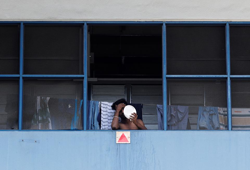 A migrant worker living in a factory-converted dormitory looks into a mirror as he serves his stay-home notice during the coronavirus outbreak here on 22 April, 2020. (PHOTO: Reuters)