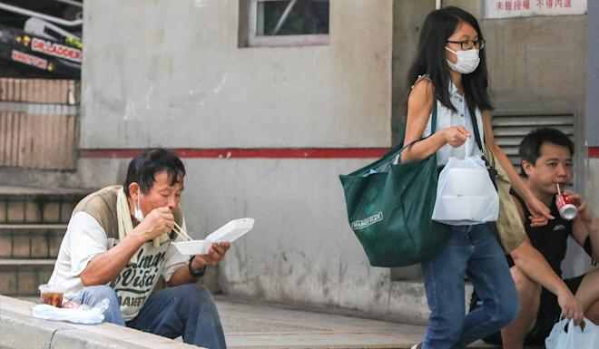 People eat their meals on the street in Central on Wednesday. Photo: May Tse