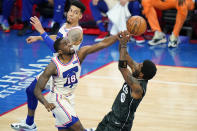 Brooklyn Nets' Kyrie Irving, right, tries to get a shot past Philadelphia 76ers' Shake Milton during the second half of an NBA basketball game, Wednesday, April 14, 2021, in Philadelphia. (AP Photo/Matt Slocum)