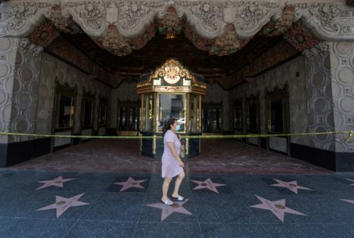 A woman walks past the famous El Capitan Theater in Hollywood, which remains closed due to the Covid-19 virus -- other theaters across the countries are reopening, and new releases will hit screens in July 2020