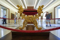 Visitors walk by a papal faldstool bearing the coat of arms of Pope Pius IX, 1846-1878, in the Papal Palace in Castel Gandolfo, some 30 kilometers southeast of Rome, Saturday, May 29, 2021. As Covid-19 restrictions are slowly being lifted in Italy, thousands of people are returning to visit the extensive gardens and apartments at the Papal Palace of Castel Gandolfo in the Alban Hills near Rome, that for hundreds of years have been the summer retreat for Popes seeking to escape the suffocating heat of Rome. (AP Photo/Andrew Medichini)