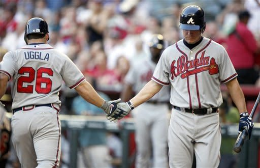 Atlanta Braves' Dan Uggla, left, is congratulated by teammate Chipper Jones, right, while returning to the dugout after hitting a solo home run off Arizona Diamondbacks pitcher Joe Saunders in the third inning of a baseball game on Saturday, April 21, 2012, in Phoenix.(AP Photo/Paul Connors)