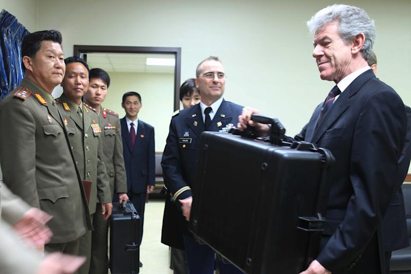 British Ambassador to North Korea Peter Hughes holds a case containing the remains thought to be of a British pilot shot down during the Korean War, at a brief ceremony with North Korean military officers and U.N. Military Armistice Commission representatives at the truce village of Panmunjom in the demilitarized zone separating North and South Korea, Wednesday May 4, 2011. North Korea handed back the remains to British representatives at Panmunjom. (AP Photo/APTN)