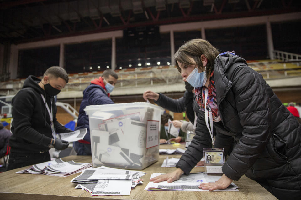 Election commission employees count casted ballots after the polls closed in parliamentary elections in capital Pristina, Kosovo on Sunday, Feb. 14, 2021. Kosovo's voters defied freezing weather to vote in an early parliamentary election to form a new government amid the coronavirus pandemic, an economic downturn and stalled negotiations with wartime foe Serbia. (AP Photo/ Visar Kryeziu)
