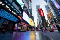 News related to coronavirus disease (COVID-19) are seen on a display at Times Square in New York City, New York