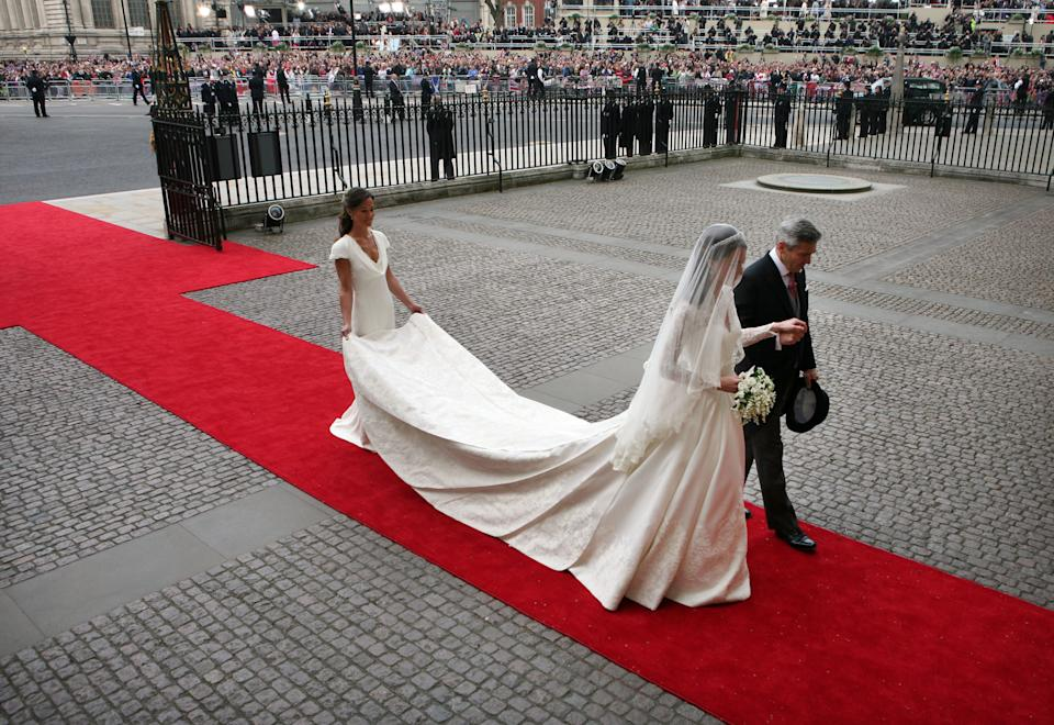 Kate Middleton is escorted by her father Michael (R) and sister Pippa (L) at Westminster Abbey for her wedding to Prince William in London April 29, 2011. REUTERS/Tom Pilston/POOL  (BRITAIN - Tags: SPORT SOCCER ROYALS ENTERTAINMENT PROFILE)