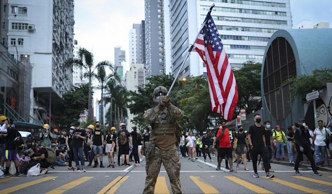 A Hong Kong protester in military costume waves a US flag. Photo: AP