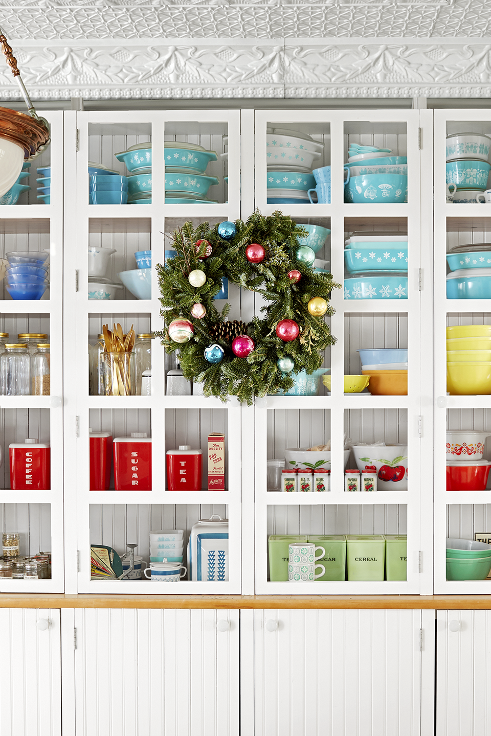 """<p>Everyone knows wreaths look great on windows and doors, but why not add them to your kitchen and pantry cabinets too? Opt for brightly hued ornaments to add punch, or neutral ones to add elegance to your wreath, and then display it on storage pieces in sight like <a href=""""https://www.countryliving.com/home-design/house-tours/g4929/farmhouse-packed-christmas-decorating-ideas/"""" rel=""""nofollow noopener"""" target=""""_blank"""" data-ylk=""""slk:these Michigan farmhouse owners did"""" class=""""link rapid-noclick-resp"""">these Michigan farmhouse owners did</a>.</p><p><a class=""""link rapid-noclick-resp"""" href=""""https://www.amazon.com/s/ref=nb_sb_noss_2?url=search-alias%3Dgarden&field-keywords=christmas+wreath&rh=n%3A1055398%2Ck%3Achristmas+wreath&tag=syn-yahoo-20&ascsubtag=%5Bartid%7C10050.g.1247%5Bsrc%7Cyahoo-us"""" rel=""""nofollow noopener"""" target=""""_blank"""" data-ylk=""""slk:SHOP CHRISTMAS WREATHS"""">SHOP CHRISTMAS WREATHS</a> </p>"""