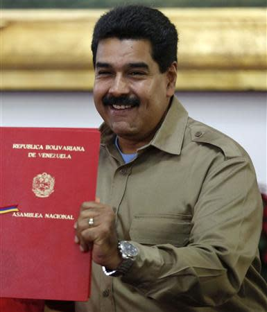 Venezuelan President Nicolas Maduro receives the document approving a law which grants him with decree powers in Caracas, November 19, 2013. REUTERS/Carlos Garcia Rawlins