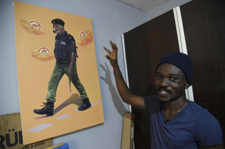 Artist Julius Agbaje shows a painting of a police officer with dog's head, entitled 'Mad Dog'