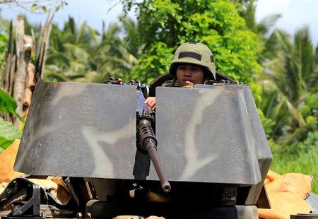 A government soldier atop an armoured personnel carrier is posted along a main highway in Pantar town, Lanao del Norte, after residents started to evacuate their hometown of Marawi city, southern Philippines May 24, 2017.     REUTERS/Romeo Ranoco