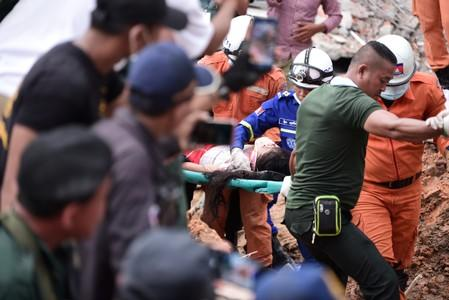 Rescue team carries a wounded worker at a collapsed building in Sihanoukville