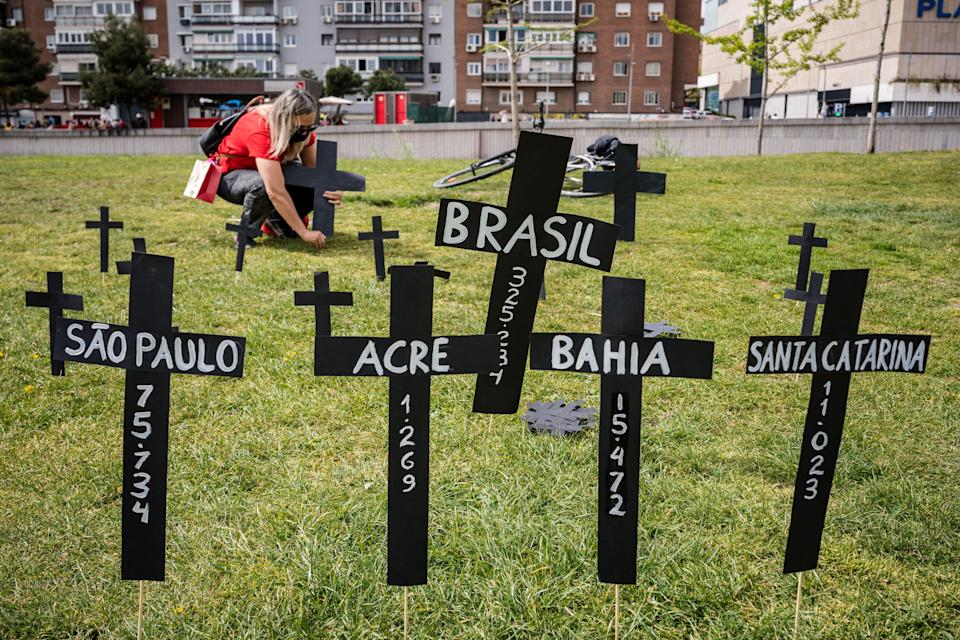 A woman lays a cross in memory of Brazil's Covid victims in the Madrid Rio park (Photo: SOPA Images via Getty Images)
