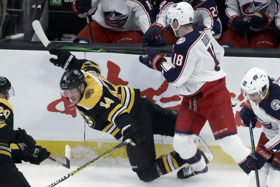 Boston Bruins right wing Chris Wagner (14) is checked along the boards by Columbus Blue Jackets center Pierre-Luc Dubois (18) in the first period of an NHL hockey game, Thursday, Jan. 2, 2020, in Boston. (AP Photo/Elise Amendola)