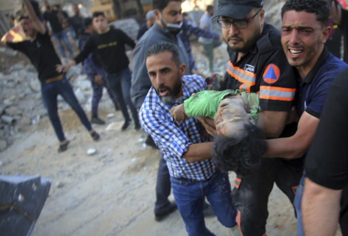 Palestinians carry the body of a child found in the rubble of a house belonging to the Al-Tanani family, that was destroyed in Israeli airstrikes in town of Beit Lahiya, northern Gaza Strip, Thursday, May 13, 2021. (AP Photo/Abdel Kareem Hana)