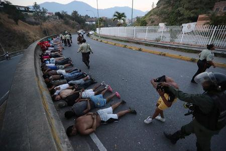 FILE PHOTO:  People detained by security forces lie on the street after looting broke out during an ongoing blackout in Caracas, Venezuela, March 10, 2019. REUTERS/Ivan Alvarado