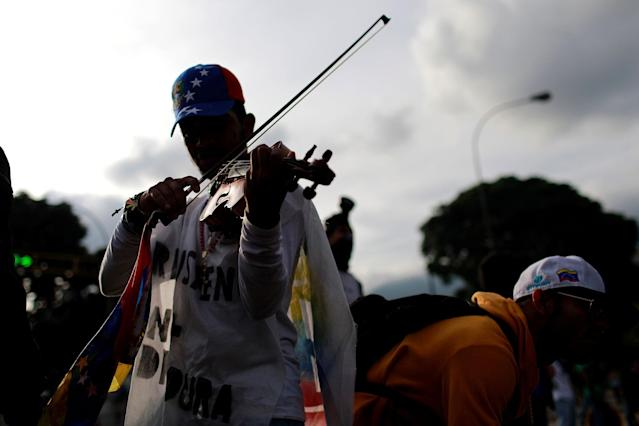 <p>A man plays a violin at a rally during a strike called to protest against Venezuelan President Nicolas Maduro's government in Caracas, Venezuela, July 27, 2017. (Photo: Marco Bello/Reuters) </p>