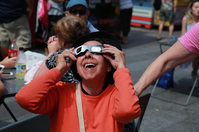 <p>People share glasses to watch the total solar eclipse in Times Square, New York City, on Aug. 21, 2017. (Gordon Donovan/Yahoo News) </p>