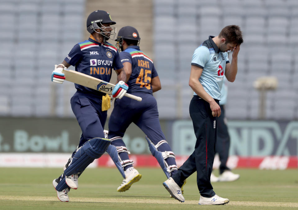England's Mark Wood, right, reacts as India's Shikhar Dhawan, left, and Rohit Sharma run between the wickets to score during the first One Day International cricket match between India and England at Maharashtra Cricket Association Stadium in Pune, India, Tuesday, March 23, 2021. (AP Photo/Rafiq Maqbool)