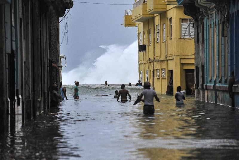 Cubans wade through a flooded street near the Malecon seafront promenade in Havana, on September 10, 2017. (AFP Photo/YAMIL LAGE)