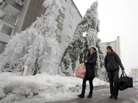 Enej Progar (R) and Armina Gasi leave their apartment after four days without electricity and heating, in Postojna February 5, 2014. REUTERS/Srdjan Zivulovic