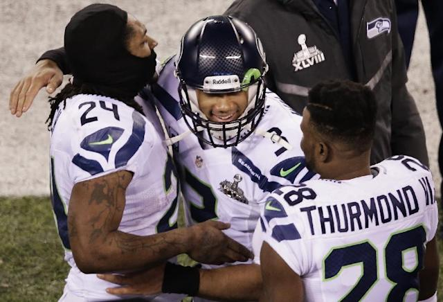 Seattle Seahawks' Russell Wilson celebrates with Marshawn Lynch and Walter Thurmond during the second half of the NFL Super Bowl XLVIII football game against the Denver Broncos Sunday, Feb. 2, 2014, in East Rutherford, N.J. The Seahawks won 43-8. (AP Photo/Charlie Riedel)