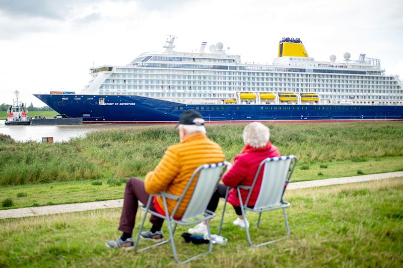 "30 August 2020, Lower Saxony, Westoverledingen: A couple sits on two chairs on the dike near the village of Dorenburg and looks at the new cruise liner ""Spirit of Adventure"", which has left the Meyer shipyard and is sailing on the Ems. The ship built for the British shipping company Saga Cruises is to be transferred to the North Sea via the Ems. Photo: Hauke-Christian Dittrich/dpa (Photo by Hauke-Christian Dittrich/picture alliance via Getty Images)"