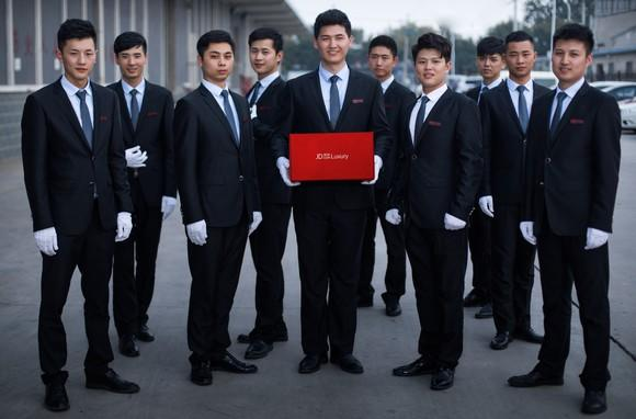 a group of young men in suits and white gloves face the camera as one holds a red box labeled with JD's logo.