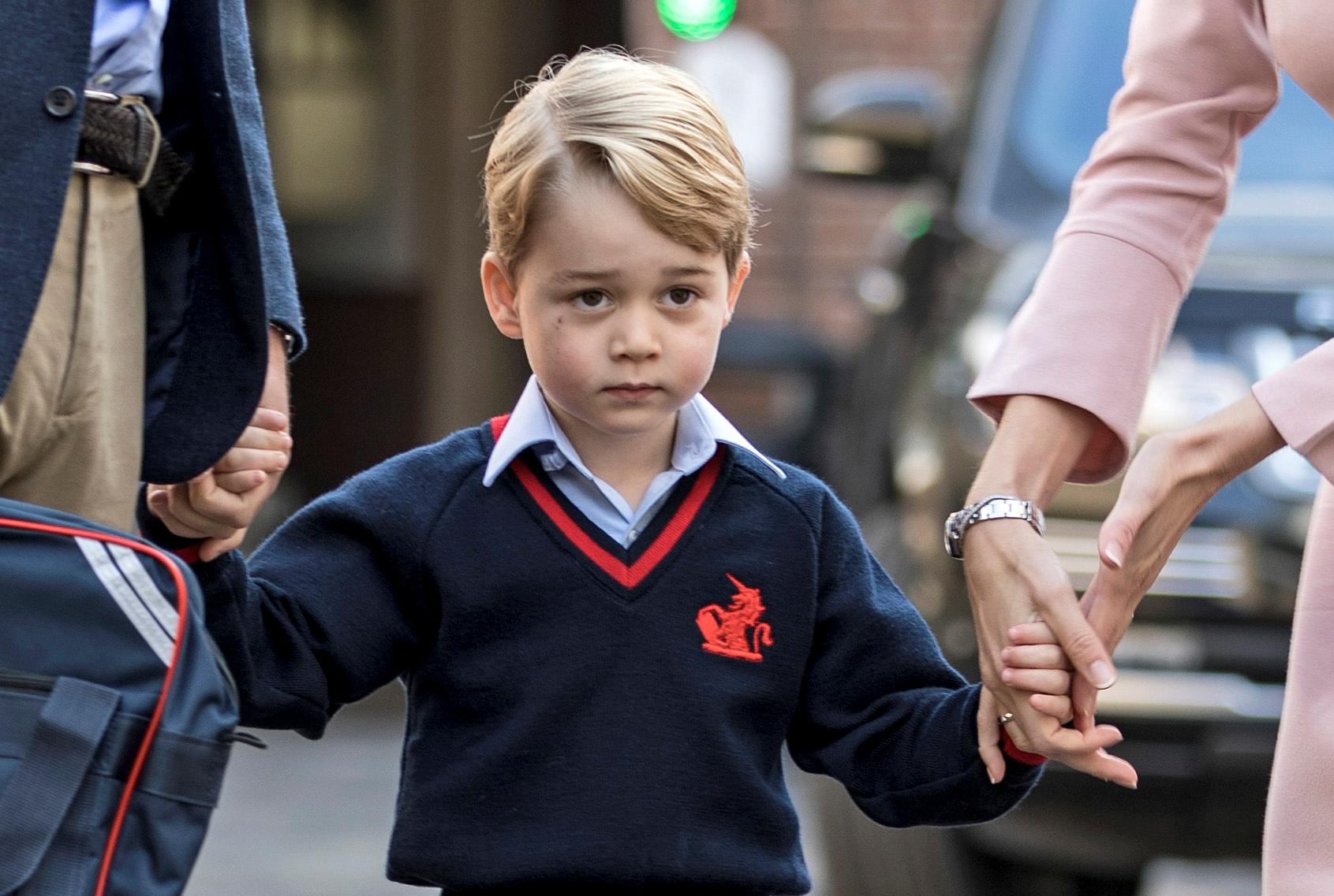 Helen Haslem, head of the lower school and Britain's Prince William hold Prince George's hands as he arrives for his first day of school at Thomas's school in Battersea, London, September 7, 2017. REUTERS/Richard Pohle/Pool