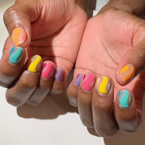 "<p>The combination of bright <a href=""https://www.cosmopolitan.com/style-beauty/g9657134/summer-nail-polish-colors/"" rel=""nofollow noopener"" target=""_blank"" data-ylk=""slk:summer nail polish"" class=""link rapid-noclick-resp"">summer nail polish</a> shades and attention-grabbing wavy lines with negative space will distract anyone from noticing the length of your nails, no matter how stubby they might be. Use a small, flat <a href=""https://www.amazon.com/FULINJOY-Drawing-Brush-Acrylic-Painting/dp/B088HFXDVM/?tag=syn-yahoo-20&ascsubtag=%5Bartid%7C10049.g.34319849%5Bsrc%7Cyahoo-us"" rel=""nofollow noopener"" target=""_blank"" data-ylk=""slk:nail brush"" class=""link rapid-noclick-resp"">nail brush</a> dipped in <a href=""https://www.bernadettethompson.com/product-page/wipe-out"" rel=""nofollow noopener"" target=""_blank"" data-ylk=""slk:nail polish remover"" class=""link rapid-noclick-resp"">nail polish remover</a> to keep the edges of your lines sharp and not wavy in a bad way.</p><p><a href=""https://www.instagram.com/p/CCM_M8JDitu/?utm_source=ig_embed&utm_campaign=loading"" rel=""nofollow noopener"" target=""_blank"" data-ylk=""slk:See the original post on Instagram"" class=""link rapid-noclick-resp"">See the original post on Instagram</a></p>"