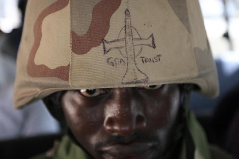 """A soldier looks out from under the brim of his helmet in Maiduguri, Nigeria, on Thursday, June 6, 2013. The writing on it reads: """"God Trust: In God All Things Are Possible"""". Maiduguri is the heart of Nigeria's Islamic insurgency. Military officials took journalists on a tour there Thursday, but largely declined to give specific answers about what's happening in the country's fight against the extremists. (AP Photo/Jon Gambrell)"""