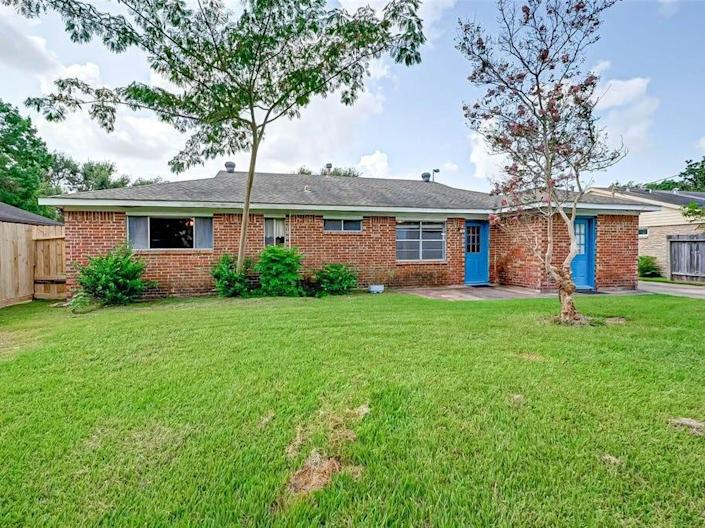 The backyard of a house for sale in houston with grass and blue doors