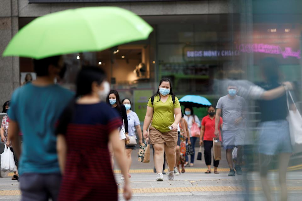 People wearing protective face masks cross a street, amid the coronavirus disease outbreak, in Singapore on 14 July, 2020. (PHOTO: Reuters)