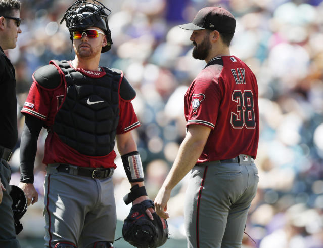 From left, umpire Chris Conroy confers with Arizona Diamondbacks catcher Carson Kelly and starting pitcher Robbie Ray as he waits to be pulled from the mound before the start of the bottom of the third inning of a baseball game against the Colorado Rockies Wednesday, Aug. 14, 2019, in Denver. Relief pitcher Matt Andriese took over on the mound for Ray. (AP Photo/David Zalubowski)