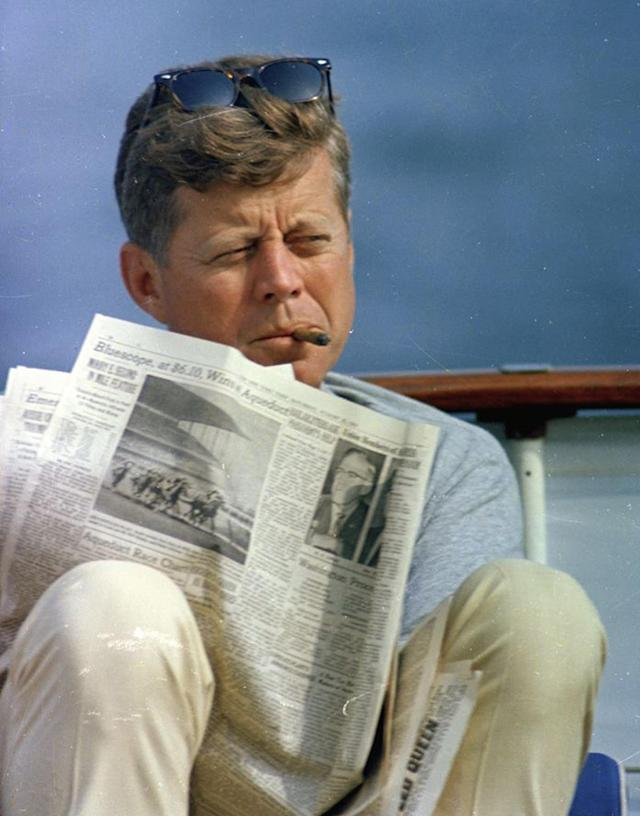 """<p>President John F. Kennedy smokes a cigar and reads the newspaper aboard the presidential yacht, the """"Honey Fitz,"""" during Labor Day weekend off the coast of Hyannis Port, Mass., Aug. 31, 1963. (Photo: Cecil Stoughton/White House/John F. Kennedy Presidential Library and Museum) </p>"""