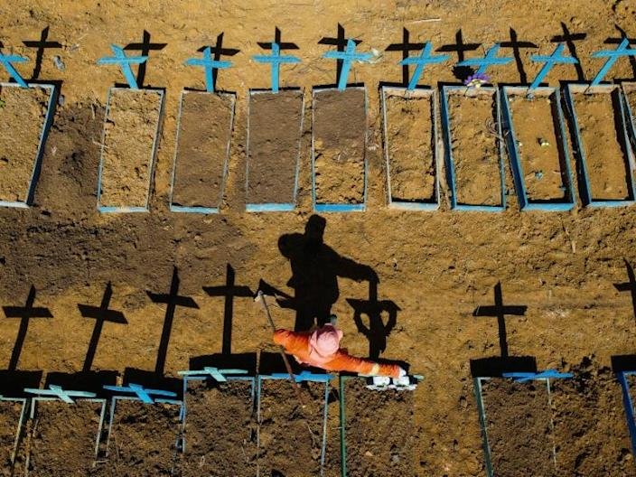Aerial view showing a gravedigger standing at the Nossa Senhora Aparecida cemetery where COVID-19 victims are buried daily, in the neighbourhood of Taruma, in Manaus, Brazil, on June 2, 2020 during the novel coronavirus pandemic.
