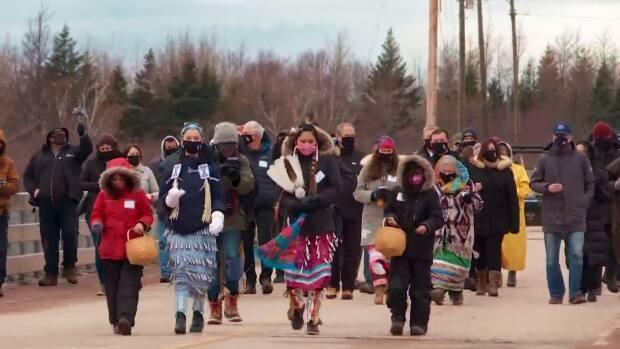 Community members and invited guests take part in a reconciliation event walking across the bridge and causeway linking Lennox Island First Nation with the rest of P.E.I. (Laura Meader/CBC - image credit)