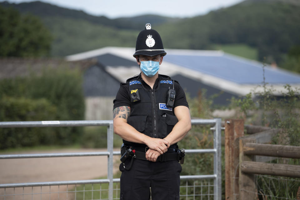 MATHON, UNITED KINGDOM - JULY 12 - JULY 12: A police officer wearing a surgical face mask stands at the entrance to AS Green and Co farm on July 12, 2020 in Mathon, Herefordshire. AS Green and Co, based in Mathon near Malvern, has said 73 of its 200 employees have COVID-19 following an outbreak there. Workers are being asked to isolate on the farm and stay within household groups to reduce the risk of spreading the virus within the workforce. (Photo by Matthew Horwood/Getty Images)