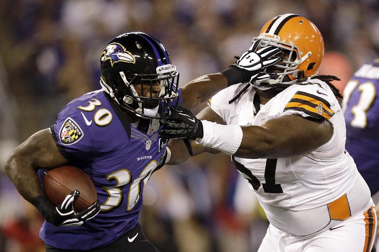 Baltimore Ravens running back Bernard Pierce fends off Cleveland Browns nose tackle Ishmaa'ily Kitchen, right, during the first half of an NFL football game in Baltimore, Thursday, Sept. 27, 2012. (AP Photo/Patrick Semansky)