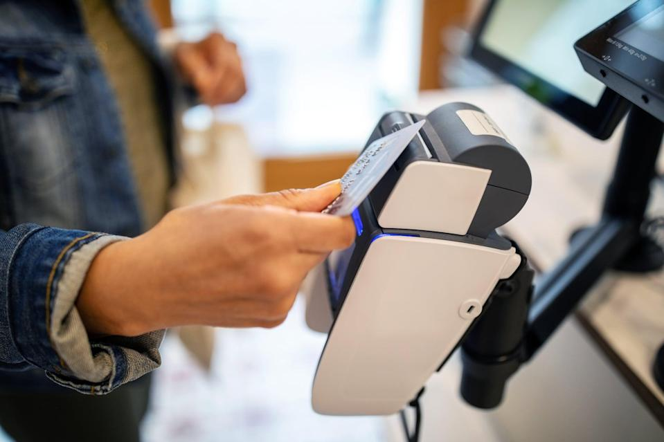 Midsection of woman using credit card for contactless payment at checkout at zero waste store