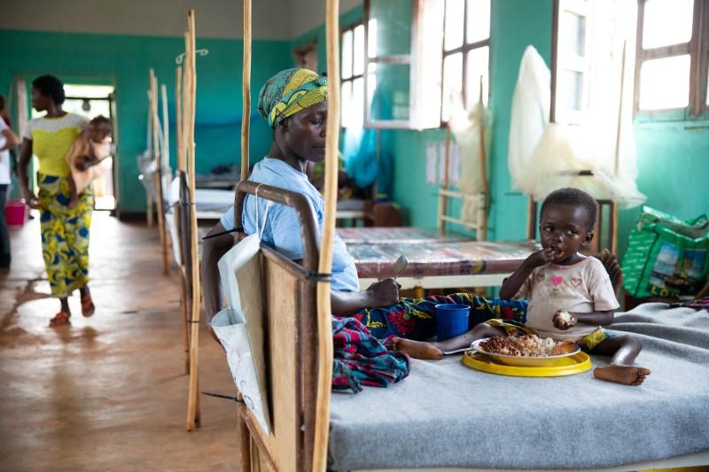 Eme Mbisa, who has become malnourished as a result of a measles infection, eats lunch with her mother, Marianne Mbisa in the measles isolation ward in Boso-Manzi hospital in Mongala province