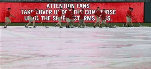 The Washington Nationals groundscrew works to keep the water off the tarp as the rain falls before a baseball game with the Atlanta Braves, Friday, June 1, 2012, in Washington. The game was postponed due to severe weather in the area. (AP Photo/Alex Brandon)