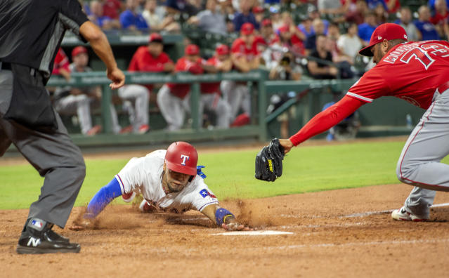 Texas Rangers' Robinson Chirinos scores ahead of the tag of Los Angeles Angels relief pitcher Osmer Morales (73) on a wild pitch by Morales during the eighth inning of a baseball game, Thursday, Aug. 16, 2018, in Arlington, Texas. Texas won 8-6. (AP Photo/Jeffrey McWhorter)